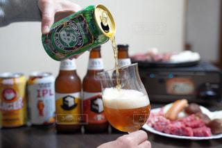 テーブルの上にビールのボトルを持っている人の写真・画像素材[2819405]