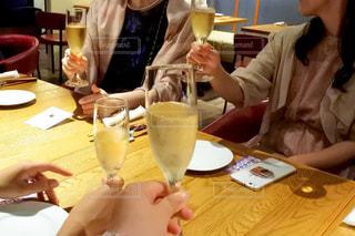 ワインを飲みながらテーブルに座っている人の写真・画像素材[3057248]