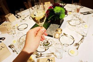 ワイングラスを持ってテーブルに座っている人の写真・画像素材[3087117]