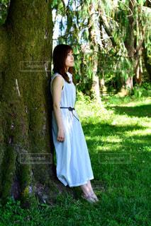 木の隣に立っている男の写真・画像素材[3146504]