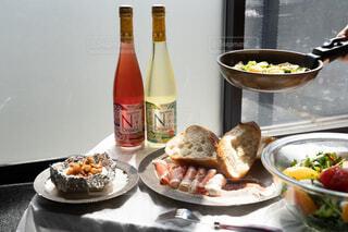 皿にワイン1本と一杯の食べ物の写真・画像素材[4300125]