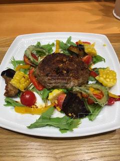 テーブルの上の野菜や肉をトッピング白プレートの写真・画像素材[1666799]