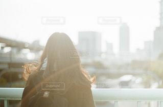 ウィンドウの前に立っている女性の写真・画像素材[1034119]