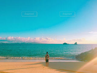 水の体の近くのビーチで2人の人々の写真・画像素材[2142145]