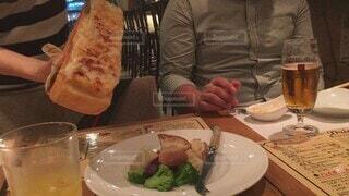 食べ物,食事,ディナー,屋内,手,フード,パン,テーブル,皿,人物,人,食器,チーズ,ビール,カップ,ブロッコリー,レストラン,フランスパン,外食,ドリンク,お洒落,夜ご飯,飲食,ラクレットチーズ