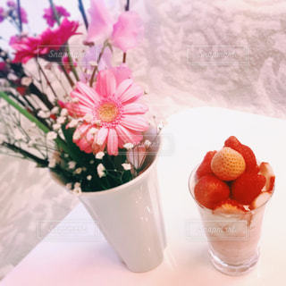 テーブルの上のピンクの花で一杯の花瓶の写真・画像素材[898311]