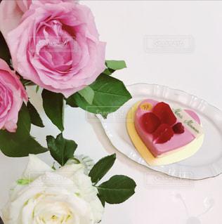 テーブルの上の花の花瓶をのせた白プレートの写真・画像素材[1230147]