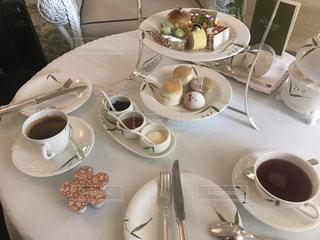 食品やコーヒー テーブルの上のカップのプレートの写真・画像素材[1256525]