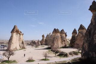 バック グラウンドでカッパドキアと大きな岩の前に立っている人々 のグループの写真・画像素材[1104297]