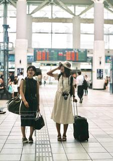 荷物の袋の横にある歩道を歩いて人々 のグループの写真・画像素材[945335]