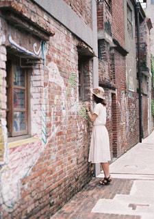 れんが造りの建物の横の道を歩いている人の写真・画像素材[952772]