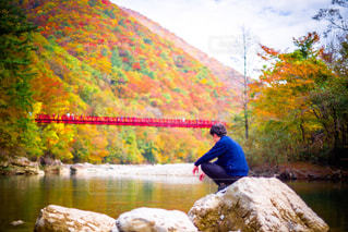 水の体の横にある岩の上に座っている男 - No.840591