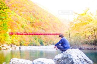 水の体の横にある岩の上に座っている男の写真・画像素材[990117]