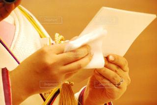 一枚の紙を持っている手の写真・画像素材[1235362]