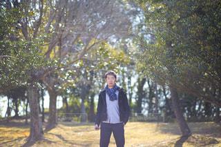 木の隣に立っている男の写真・画像素材[1023505]