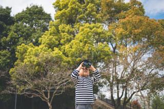 木の隣に立っている人の写真・画像素材[4428613]