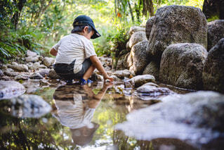 滝の隣に立っている男の写真・画像素材[4428619]