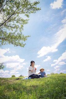 草の中に座っている人々のグループの写真・画像素材[4467195]