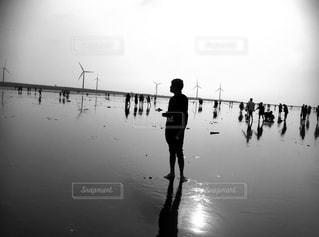 水の体の横に立っている人の写真・画像素材[813509]