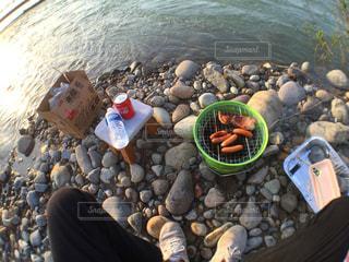 水の体の横にある岩の上に座っている人々 のグループの写真・画像素材[1208645]