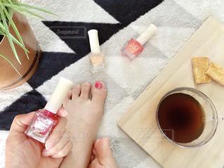 ネイル中の女性の手足とコーヒーの写真・画像素材[1213979]