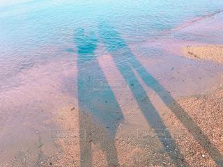 波打ち際に長く伸びる親子3人の影の写真・画像素材[1314351]