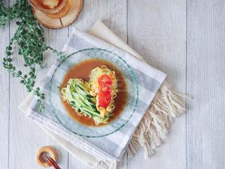 木製のテーブルの上に座っている食べ物のボウルの写真・画像素材[2279179]