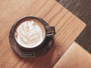 木製のテーブルの上に座っているコーヒー1杯の写真・画像素材[2287296]