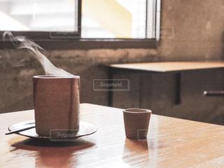 木製のテーブルの上に座っている鳥の写真・画像素材[2301994]