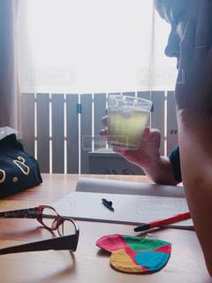 女性,窓,手,指輪,氷,テーブル,逆光,横顔,木製,冷たい,一息,緑茶,日本茶,コースター,仕事中,ボールペン,休憩中,メガネ,上半身,パーティション,頬づえ
