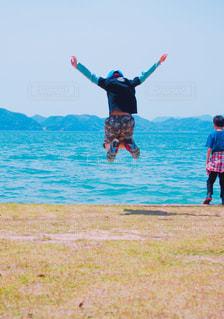 瀬戸内海に向かってジャンプする少年の写真・画像素材[1167957]