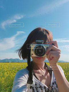 菜の花畑と撮影中の私の写真・画像素材[1218103]