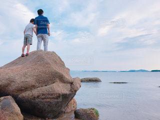 大きい岩の上で話す親子の写真・画像素材[1245778]