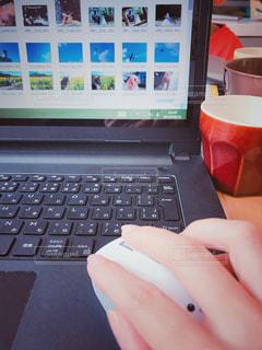 コーヒー飲みつつパソコン作業中の写真・画像素材[1525606]
