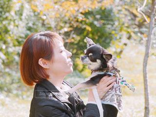 公園で散歩中、愛犬を抱っこの写真・画像素材[1585432]