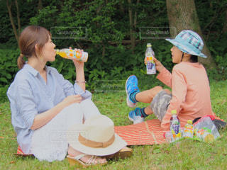公園でジュース片手に談笑中の親子の写真・画像素材[2214390]