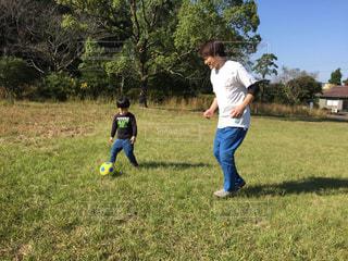 フィールド上にサッカー ボールを抱いて少年の写真・画像素材[968941]