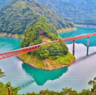 背景の山が付いている水の体の上の橋 - No.781852