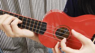 ギターを抱えて赤いシャツの女性の写真・画像素材[821524]