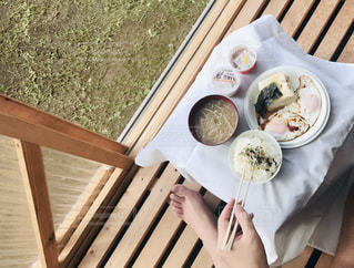 食品のプレートをテーブルに座っている女性の写真・画像素材[1490738]