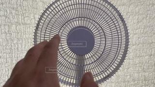 扇風機に手をかざす。夏のひとこまの写真・画像素材[3466594]