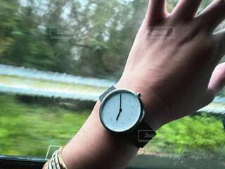 腕時計をつけた左手を車の窓にかざす。憂鬱な雨降りの休日の写真・画像素材[3791474]