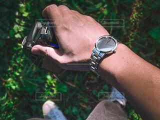 カメラを持つ男性の手とブラック文字版とシルバーのベルトの腕時計の写真・画像素材[3791536]