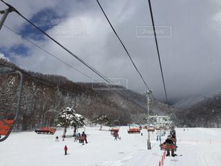 雪に覆われた斜面をスキーに乗っている人のグループ - No.930667