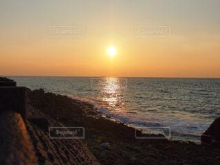 海の横にあるビーチに沈む夕日の写真・画像素材[1288769]