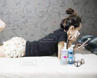 ラップトップを使用してベッドの上に座っている女性の写真・画像素材[720144]