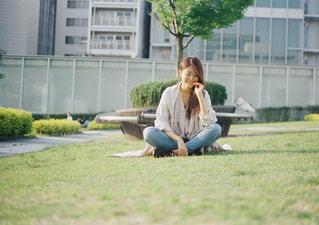 草の上に座っている女性の写真・画像素材[1235556]