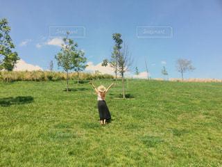 緑豊かな緑のフィールドに立っている人の写真・画像素材[711049]