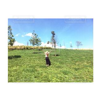 緑豊かな緑のフィールドに立っている人の写真・画像素材[1161574]