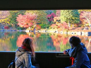 池の前で立っている女性の写真・画像素材[881123]
